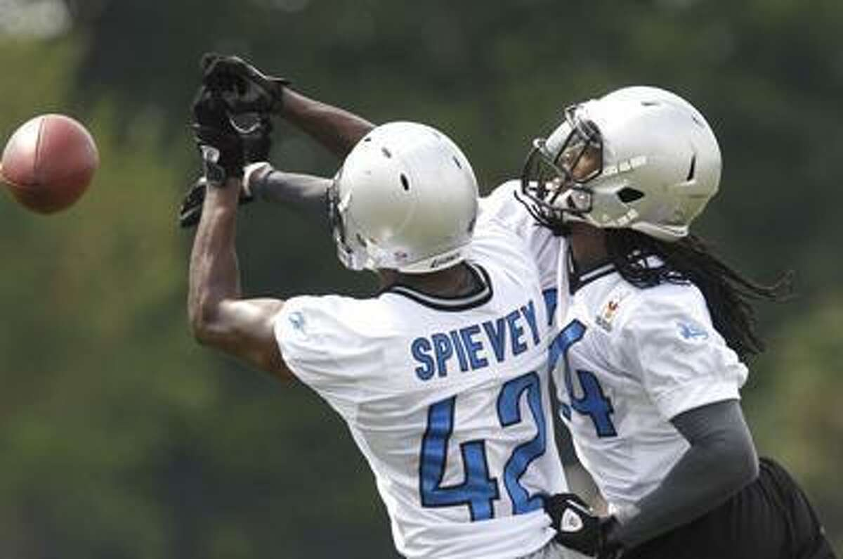 Detroit Lions cornerback Jonathan Wade, right, covers teammate Amari Spievey, deflecting a pass during drill at NFL football training camp in Allen Park, Mich., Aug. 2. (AP)