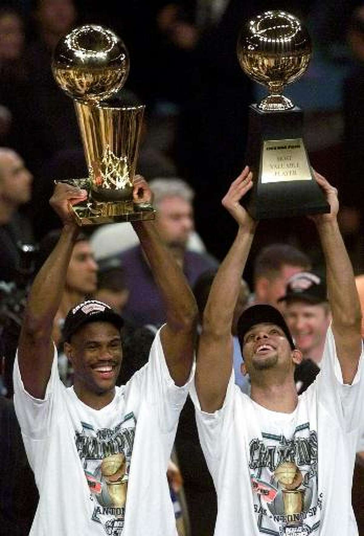 San Antonio Spurs' David Robinson, left, holds up the NBA Championship trophy as teammate Tim Duncan holds up the Most Valuable Player trophy after defeating the New York Knicks 78-77 in Game 5 of the 1999 NBA Finals Friday, June 25, 1999, at New York's Madison Square Garden. (AP Photo/Mark Lennihan)