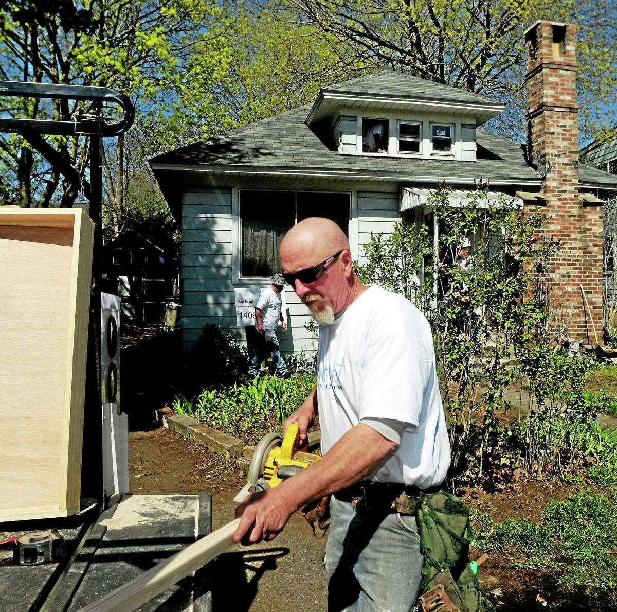 Union carpenter Tom Robison of Ansonia, a HomeFront Inc. volunteer, prepares to cut wood during a renovation project Saturday at the Malewicki residence on Whitney Avenue in Milford.