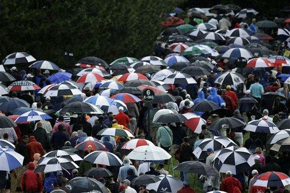 Spectators walk off the course during a second weather delay during the first round of the U.S. Open golf tournament at Merion Golf Club, Thursday, June 13, 2013, in Ardmore, Pa. (AP Photo/Julio Cortez)