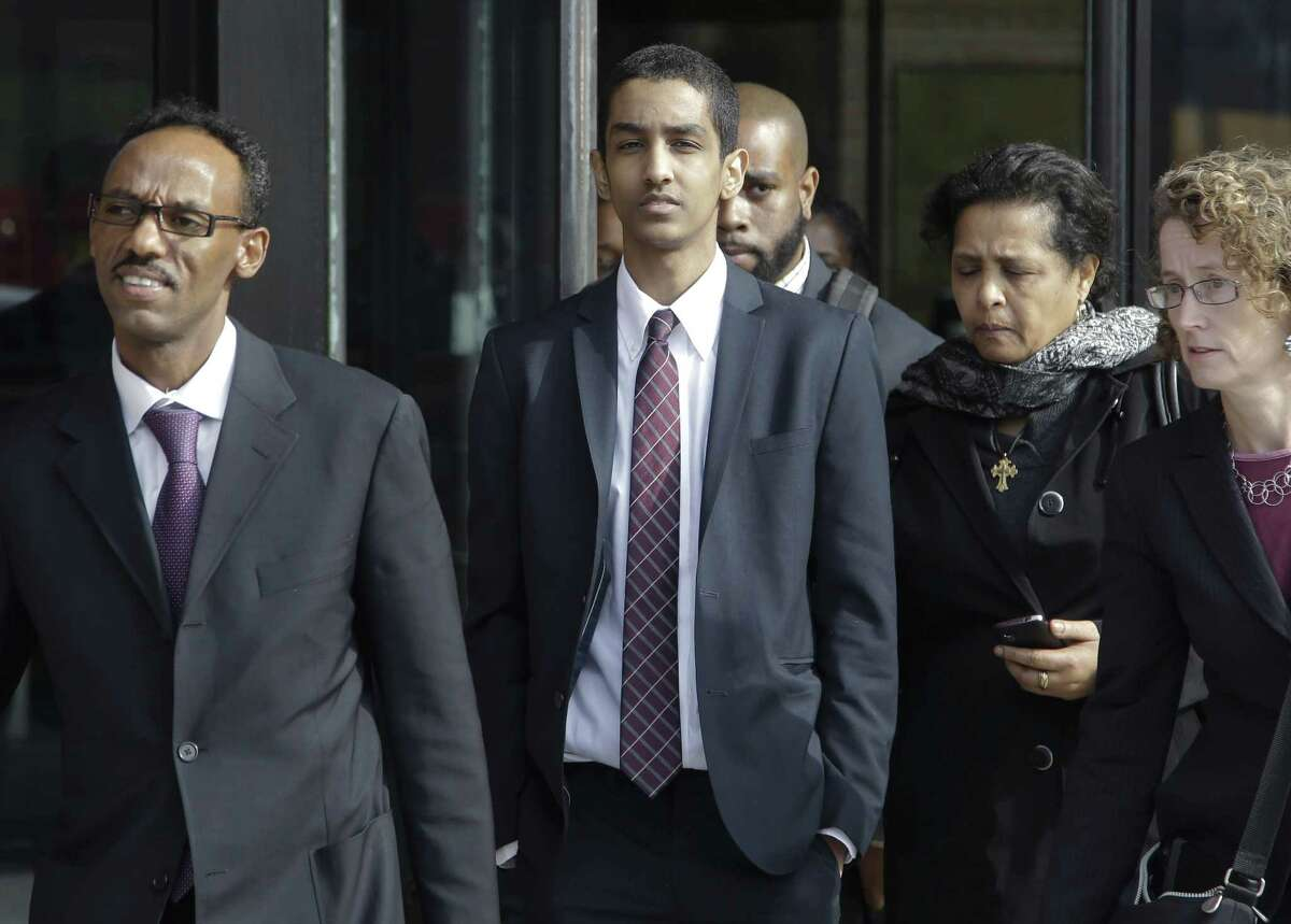 Robel Phillipos, center, departs federal court with defense attorneys Derege Demissie, left, and Susan Church, far right, after he was convicted in Boston Tuesday, Oct. 28, 2014 on two counts of lying about being in the dorm room of Boston Marathon bombing suspect Dzhokhar Tsarnaev three days after the bombing in 2013, while two other friends removed a backpack containing fireworks and other potential evidence. (AP Photo/Stephan Savoia)