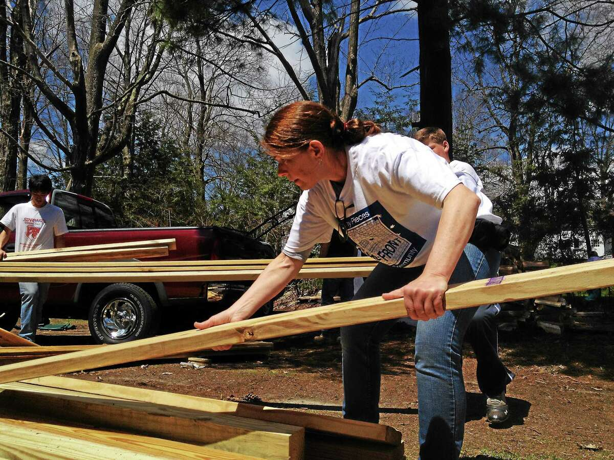 Maureen Brinchman, of Litchfield, a volunteer, stacks piles of wood during the 27th annual HomeFront Day Saturday.