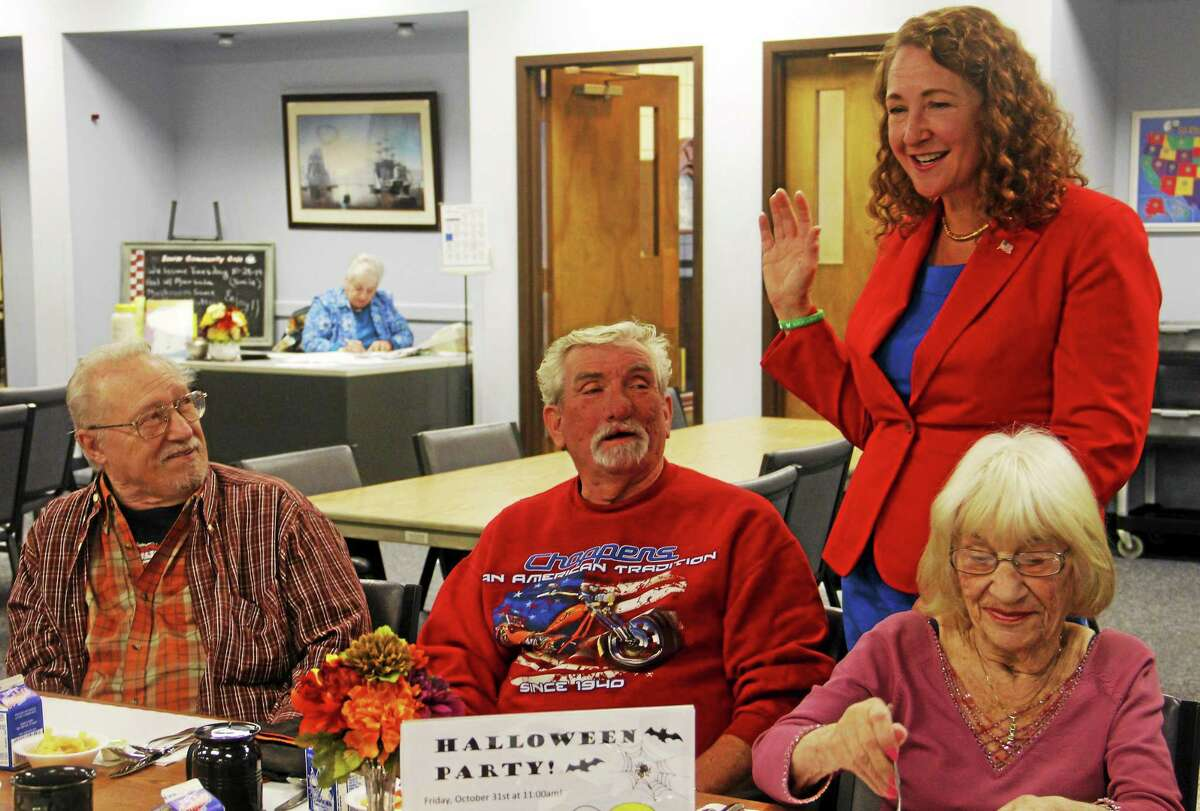 Visitors at the Sullivan Senior Center discuss one of U.S. Rep. Elizabeth Esty's television ads during a meet and greet Tuesday in Torrington.