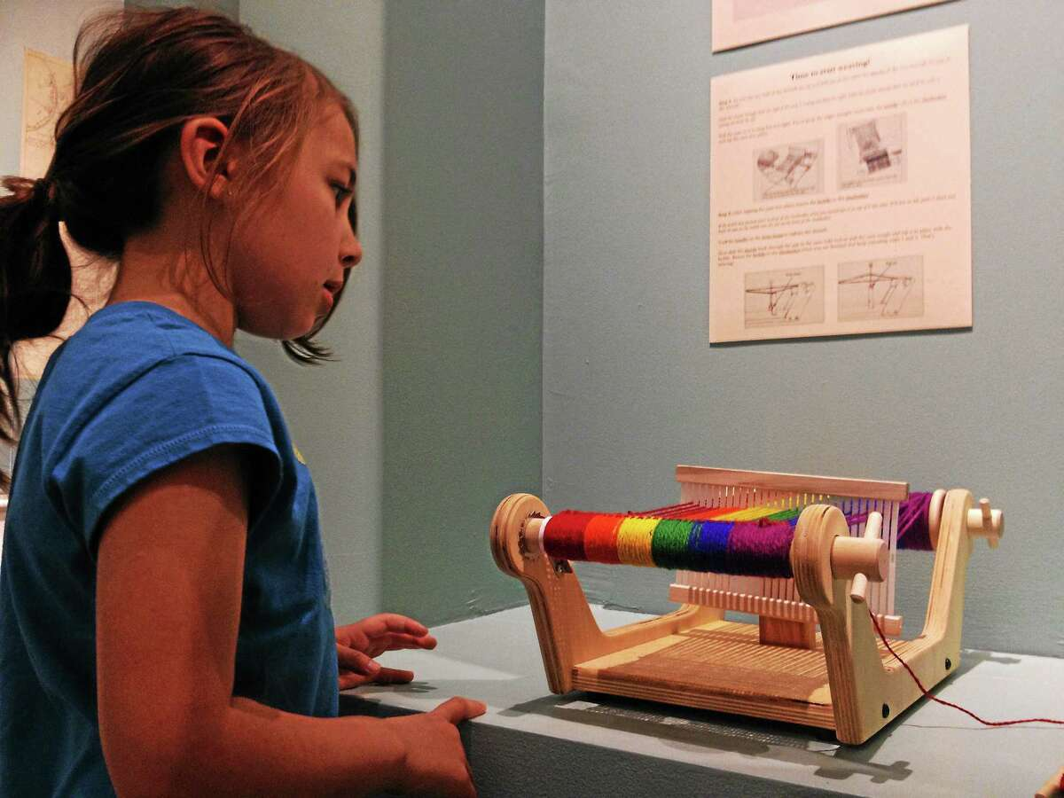 Clarissa Tranquillo, 6, looks at a weaving tool during the Litchfield History Museum Family Day on Saturday, May 3, 2014, in Litchfield. Esteban L. Hernandez Register Citizen