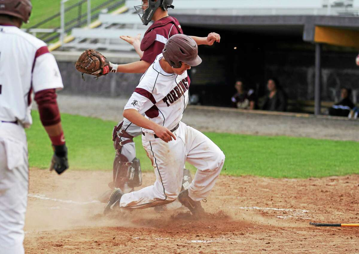 Torrington's Nate Manchester steals home during a game against Sacred Heart. The Red Raiders won 12-6.