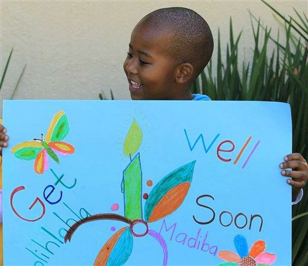 A young boy from Othandweni Community Center holds a placard wishing former South African President Nelson Mandela a prompt recovery outside his residence in Johannesburg, South Africa, Wednesday, June 12, 2013. Mandela, remains in hospital for a fifth day. The 94-year-old icon was hospitalized on Saturday for a recurring lung infection. (AP Photo/Themba Hadebe)