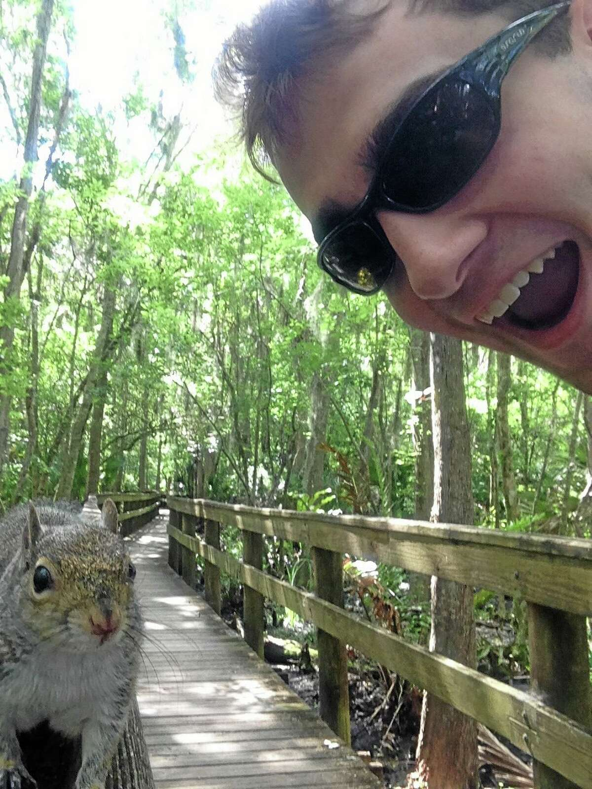 A squirrel approaches Brian Genest as he takes a photo of himself at John Chestnut Park near Tampa, Florida.