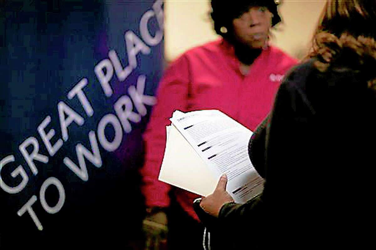 FILE - In this Thursday, Nov. 14, 2013, file photo, Jimmetta Smith, of Lithonia, Ga., right, the wife of a U.S. Marine veteran, holds her resume while talking with Rhonda Knight, a senior recruiter for Delta airlines, at a job fair for veterans and family members at the VFW Post 2681, in Marietta, Ga. The Labor Department issues the November jobs report on Friday, Dec. 6, 2013. (AP Photo/David Goldman, File)