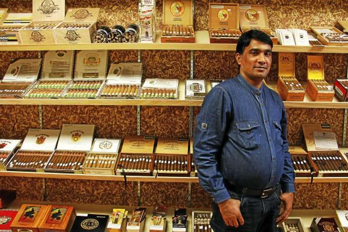 Anowar Hossan poses inside a walk-in humidor at Tobacco Mart in Torrington on Wednesday, June 12, 2013. Hossan is a Torrington resident from Bangladesh, a country located east of the Indian subcontinent in southern Asia, and he is the owner of Tobacco Mart, a tobacco and tobacco goods shop in Torrington Plaza on South Main Street that opened on June 3. Esteban L. Hernandez -- Register Citizen