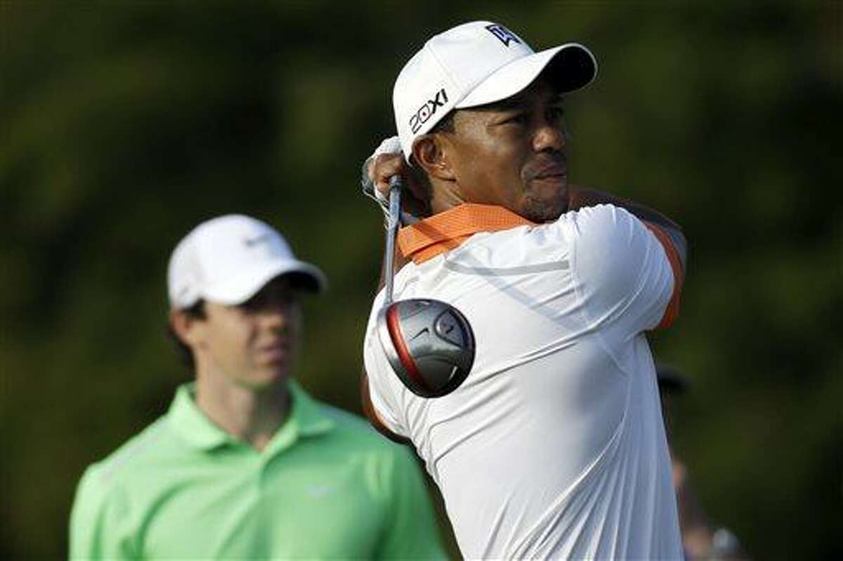 Tiger Woods tees off on the 14th hole as Rory McIlroy, of Northern Ireland, watches during practice for the U.S. Open golf tournament at Merion Golf Club, Wednesday, June 12, 2013, in Ardmore, Pa. (AP Photo/Morry Gash)