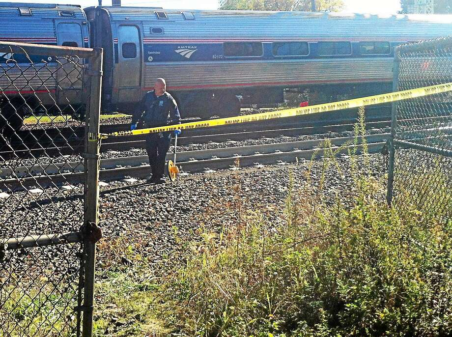 Investigators from Amtrak and the Metropolitan Transit Authority collect evidence Monday afternoon from the train tracks just west of the Milford Metro-North station. MTA officials said a female trespasser was fatally struck by an Amtrak train. Photo: Wes Duplantier — New Haven Register