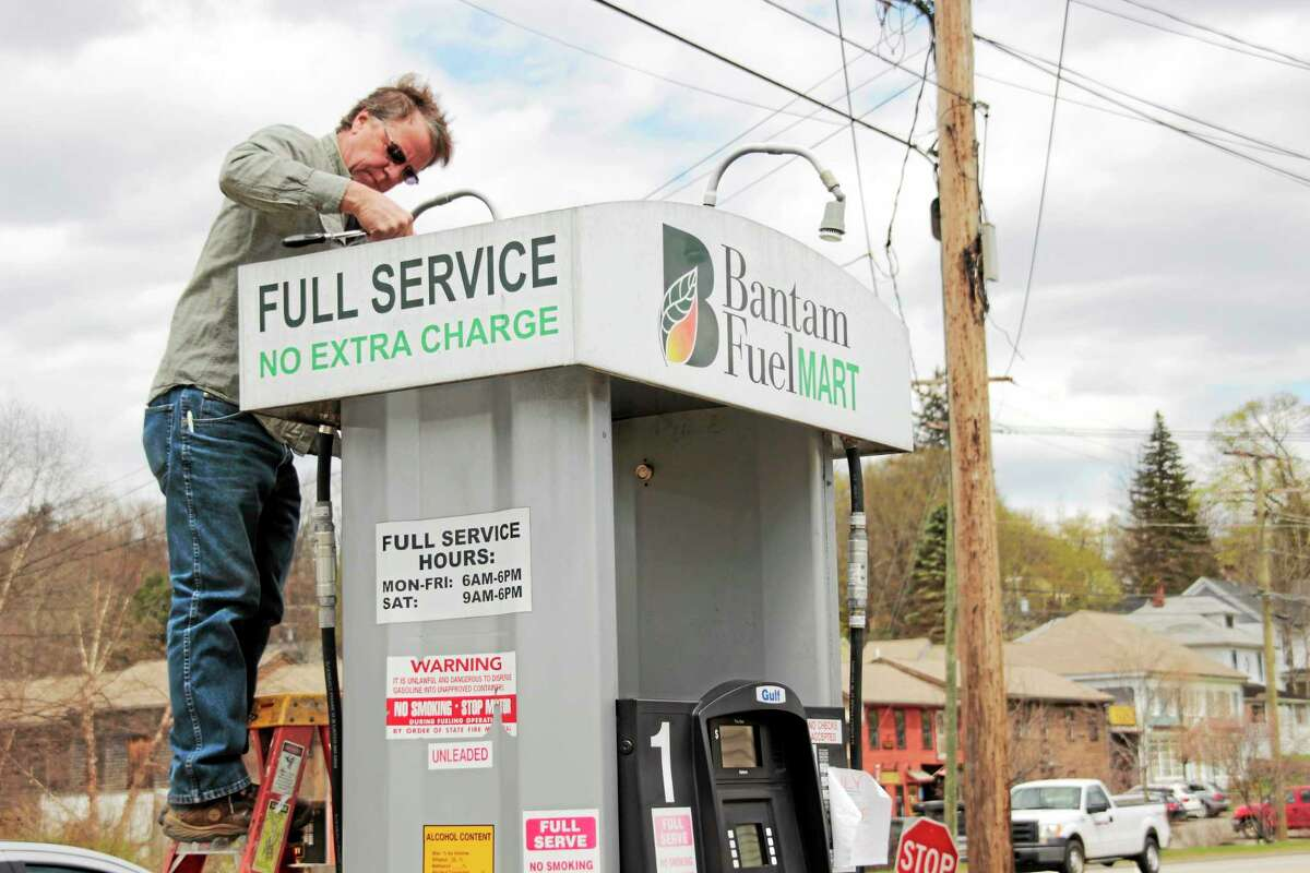 A worker pulls the signs of the Bantam Fuel Mart in Litchfield.
