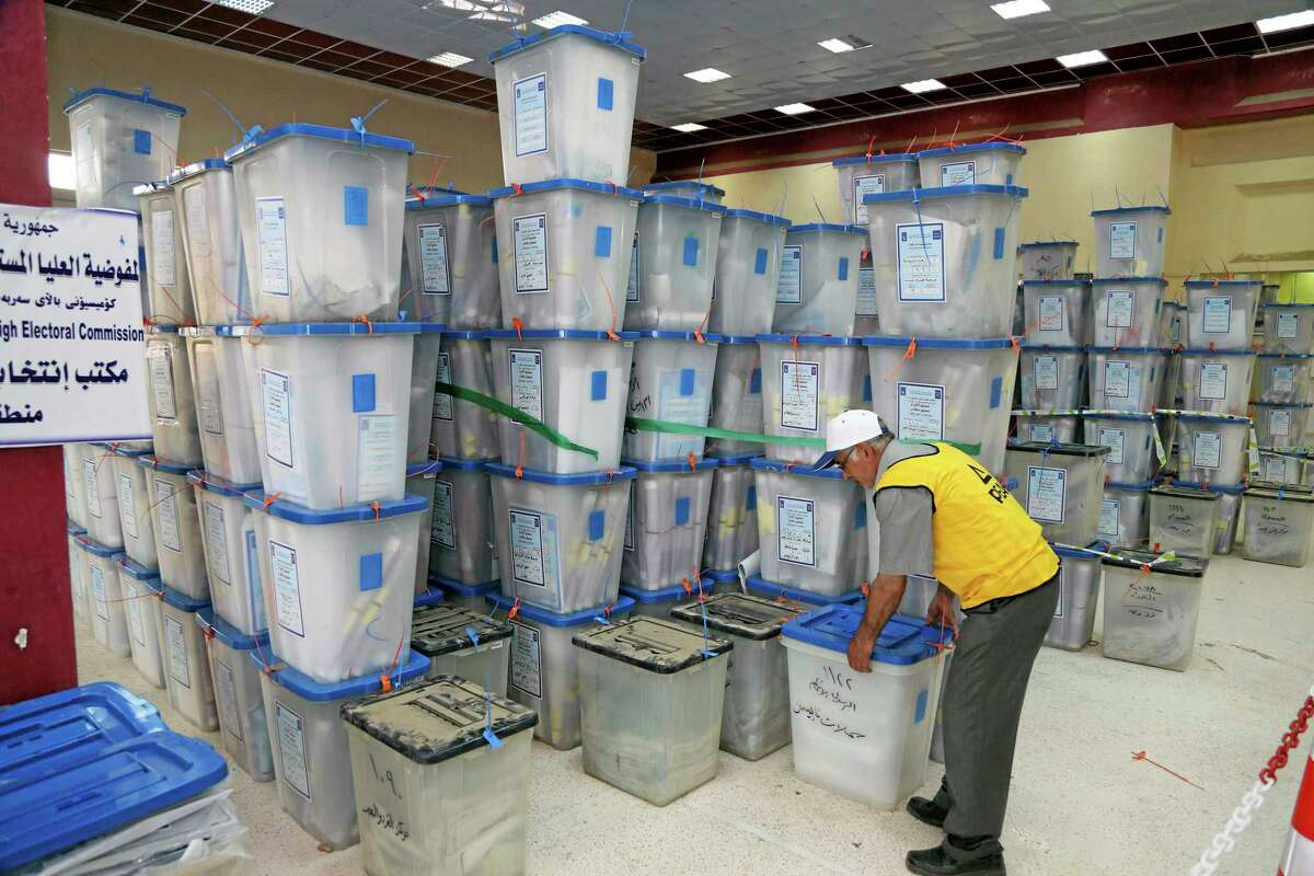 An electoral worker picks up a ballot box at a counting center in Baghdad, Iraq, Friday. Iraq voted Wednesday in its first nationwide election since U.S. troops withdrew in 2011, with Prime Minister Nouri al-Maliki confident of victory and even offering an olive branch to his critics by inviting them to join him in a governing coalition.