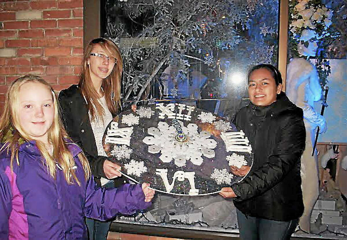 From left to right, Kate Lewton, Corina Wallenta and Leslie Tapia Bernal present the clock they designed that is part of the hidden message in the holiday window design they created in CAFTA's Main Street window.
