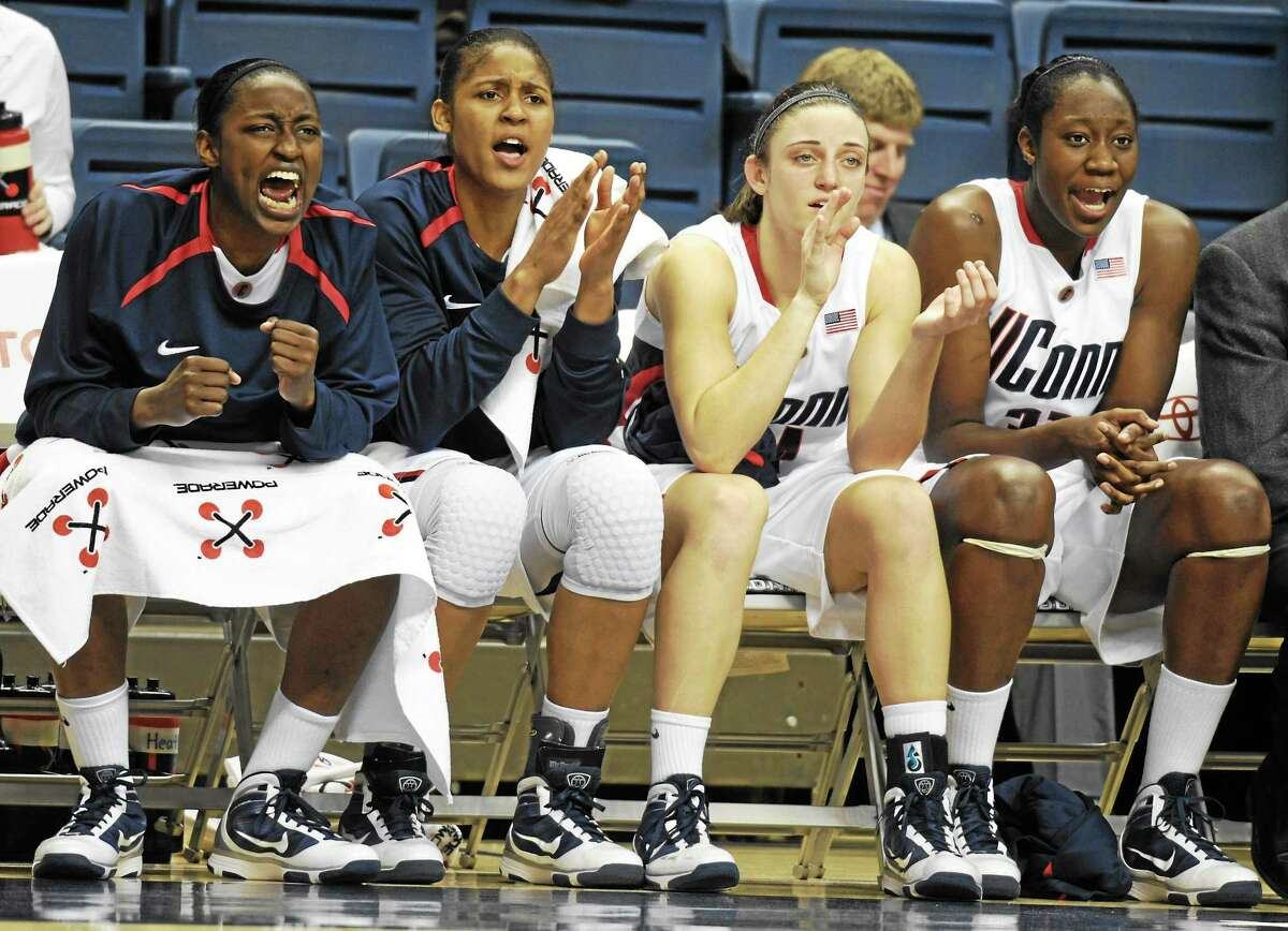 From left, Kalana Greene, Maya Moore, Kelly Faris and Tina Charles cheer on their teammates during a 2009 exhibition game against Saint Rose in Storrs.