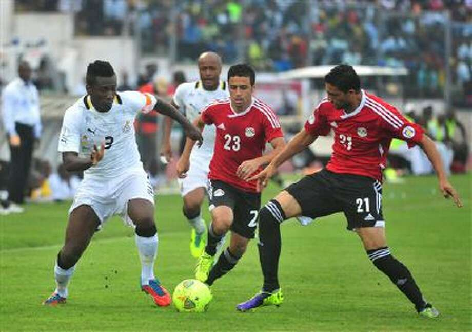 Ghana's Asamoah Gyan, left, battles with Egypt's Mohamed Naguib and Ahmed Shedid, right, during their World Cup playoff soccer match in Kumasi, Ghana, Tuesday, Oct. 15, 2013. Ghana stunned Egypt 6-1 in the first leg of their World Cup playoff on Tuesday, with Gyan's fifth-minute goal kicking off a dominant performance that makes the Black Stars overwhelming favorites to be one of the five African teams in Brazil next year. Photo: AP / AP
