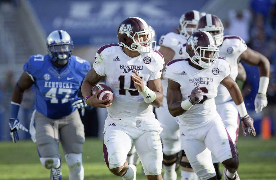 Mississippi State quarterback Dak Prescott, center, runs for a first down during the first half against Kentucky on Saturday. Photo: David Stephenson — The Associated Press  / FR171246 AP