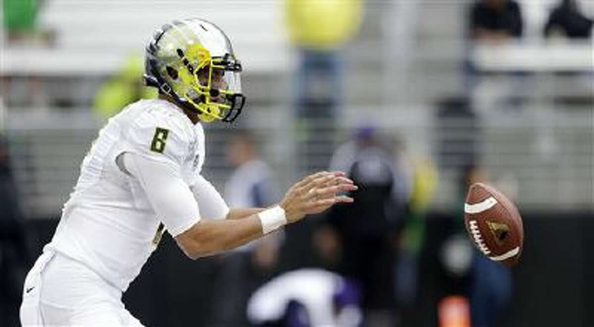 Oregon quarterback Marcus Mariota takes a snap before an NCAA college football game against Washington, Saturday, Oct. 12, 2013, in Seattle.