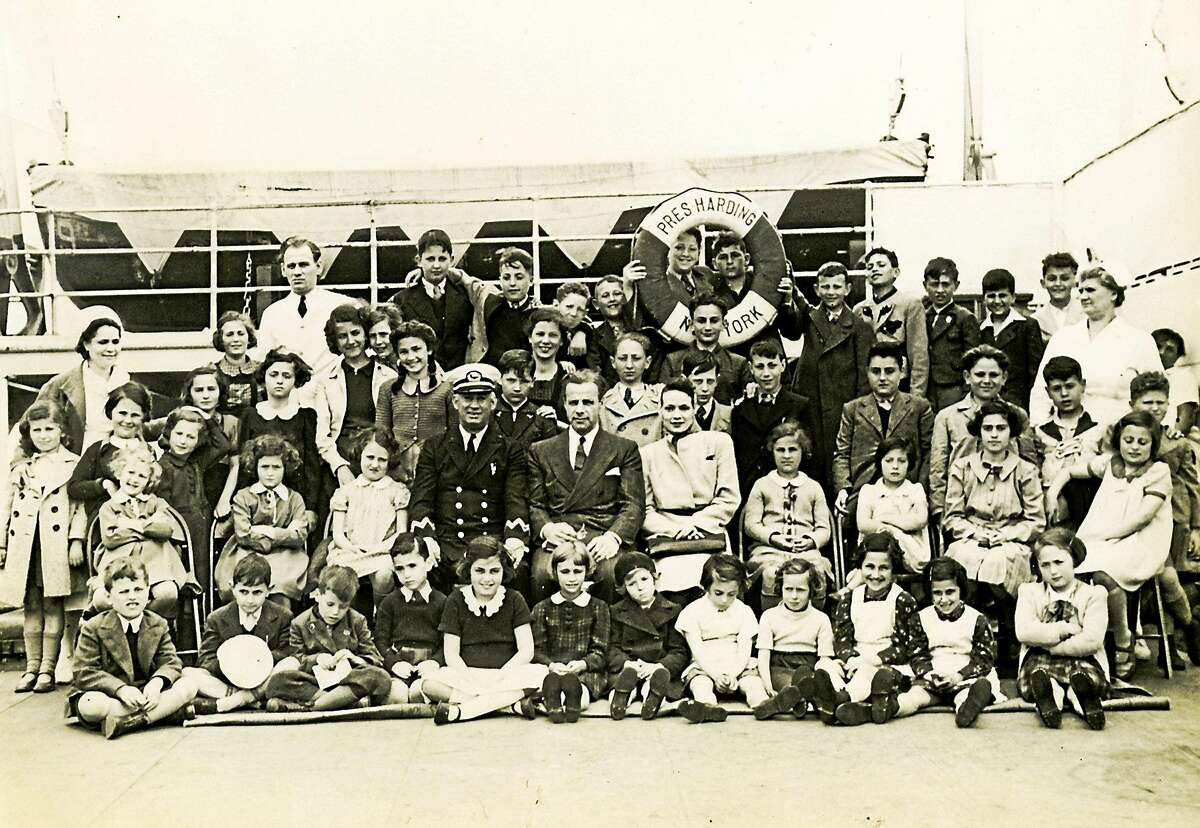 Eleanor and Gilbert Kraus and the captain of the ship, surrounded by their 50 rescued children. Photo provided by Rabbi Alvin Wainhaus