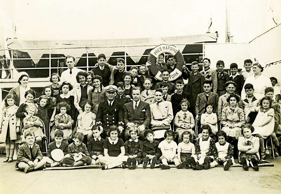 Eleanor and Gilbert Kraus and the captain of the ship, surrounded by their 50 rescued children. Photo provided by Rabbi Alvin Wainhaus Photo: Journal Register Co.