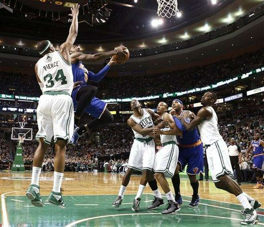 New York Knicks' J.R. Smith (8) drives to the basket past Boston Celtics' Paul Pierce (34) as Jordan Crawford, right, Avery Bradley, and Jeff Green, left, fight Knicks' Carmelo Anthony for position during the second quarter of a, NBA basketball game in Boston, Tuesday, March 26, 2013. (AP Photo/Winslow Townson) Photo: ASSOCIATED PRESS / AP2012