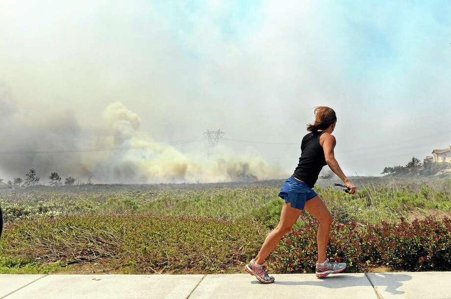 A resident talks on her phone as she watches the Etiwanda Fire in Rancho Cucamonga, Calif., Wednesday, April 30, 2014. The wildfire driven by surging Santa Ana winds sent a choking pall of smoke through foothill neighborhoods, forcing the evacuation of at least 1,650 homes and the closure of at least seven schools. No homes burned, but the smoke prompted mandatory evacuation orders for several areas of town nestled at the base of the San Bernardino Mountains east of Los Angeles. More than 500 firefighters battled the flames near this city of 165,000 people. The fire was reported about 8 a.m., grew to 200 acres by noon, quadrupled in size within a few hours and continued to grow as it roared through dry brush.(AP Photo/Inland Valley Daily Bulletin, Will Lester) Photo: AP / Inland Valley Daily Bulletin