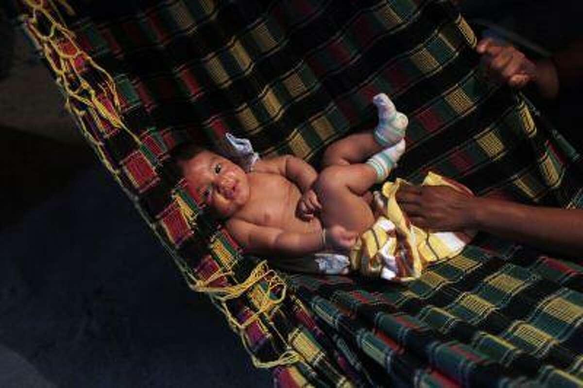 A baby rests on a hammock. REUTERS/Pilar Olivares