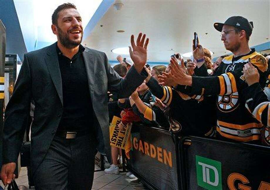 Boston Bruins left wing Milan Lucic high fives fans as the NHL hockey team departs the TD Garden in Boston for Chicago on Tuesday, June 11, 2013. The Bruins are scheduled to face the Chicago Blackhawks in Game 1 of the Stanley Cup finals on Wednesday. (AP Photo/The Boston Herald, Nancy Lane) Photo: AP / AP