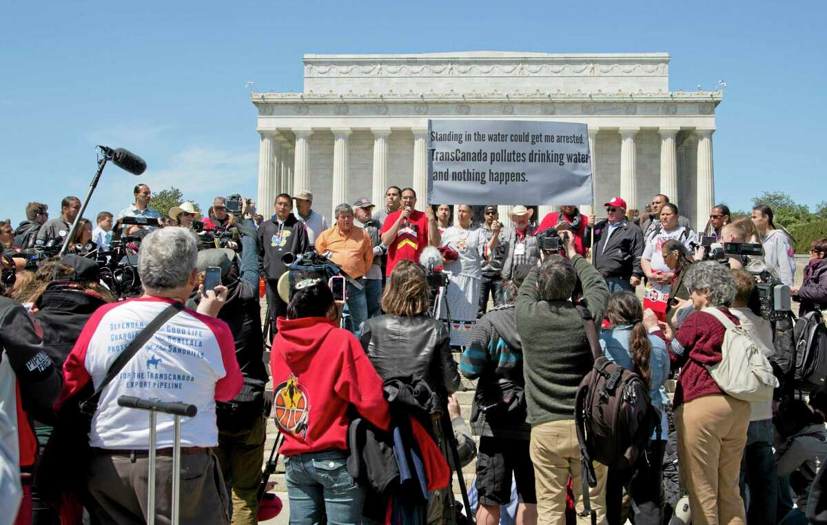 Wizipan Little Elk of the Rosebud Sioux Tribe, back center red shirt, speaks during a rally attended by an alliance of Native Americans, cowboys, ranchers and farmers, protesting the proposed Keystone XL oil pipeline, Thursday, April 24, 2014, near the Lincoln Memorial on the National Mall in Washington. (AP Photo/Manuel Balce Ceneta)
