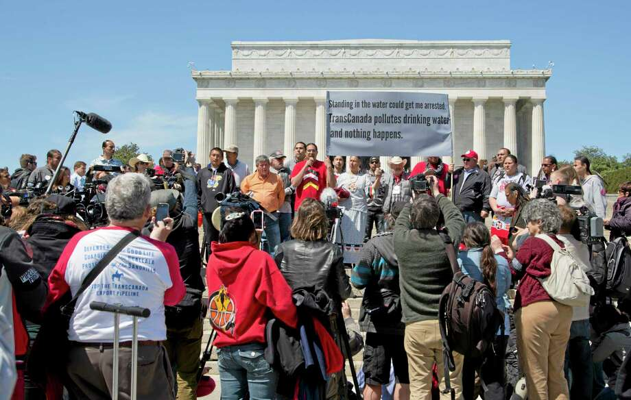 Wizipan Little Elk of the Rosebud Sioux Tribe, back center red shirt, speaks during a rally attended by an alliance of Native Americans, cowboys, ranchers and farmers, protesting the proposed Keystone XL oil pipeline, Thursday, April 24, 2014, near the Lincoln Memorial on the National Mall in Washington. (AP Photo/Manuel Balce Ceneta) Photo: AP / AP