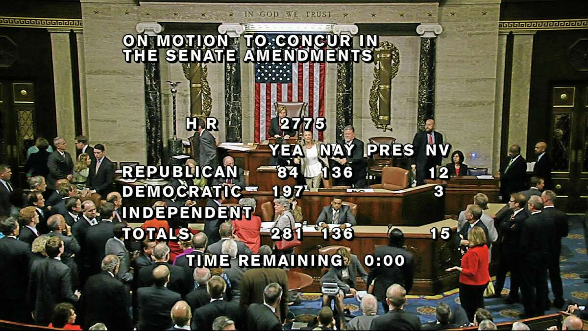 """In this image from House Television, with partial voting totals on the screen, a woman, at the rostrum just below the House presiding officer, seen between the """"yea"""" and """"nay"""" wording, is removed from the House chamber after she began shouting during the vote for the bill to end the partial 16-day government shutdown and to fund the government. The woman was described by lawmakers and aides as a long-time House stenographer. (AP Photo/House TV)"""
