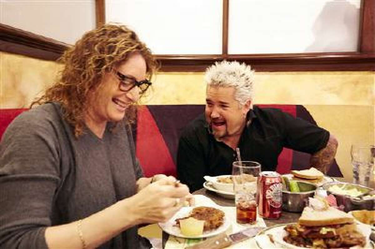 This Dec. 9, 2013 photo shows Food Network star Guy Fieri, right, with comedian Judy Gold as she prepares to taste a plate of latkes at Ben's Deli during a tour of locations for Super Bowl food in New York.