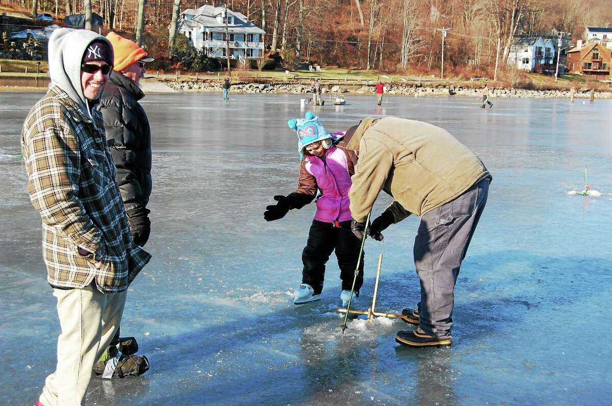 Morgan Demarest, 9, of Bethlehem, and others watch as a line is put into the ice at Highland Lake during the Northwest Sporting Goods & Supply's 2nd Annual Ice Fishing Tournament on Sunday.