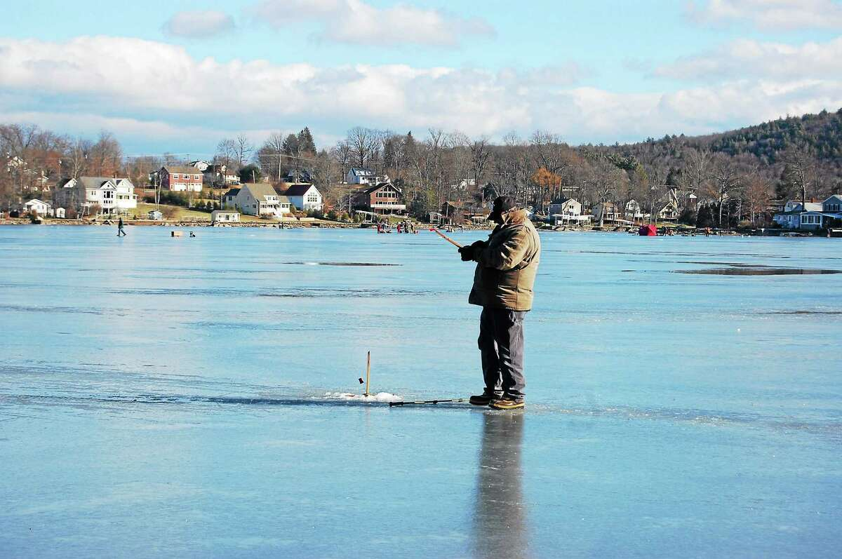 A fisherman waits for a bite at Highland Lake on Sunday during the ice fishing derby held there.