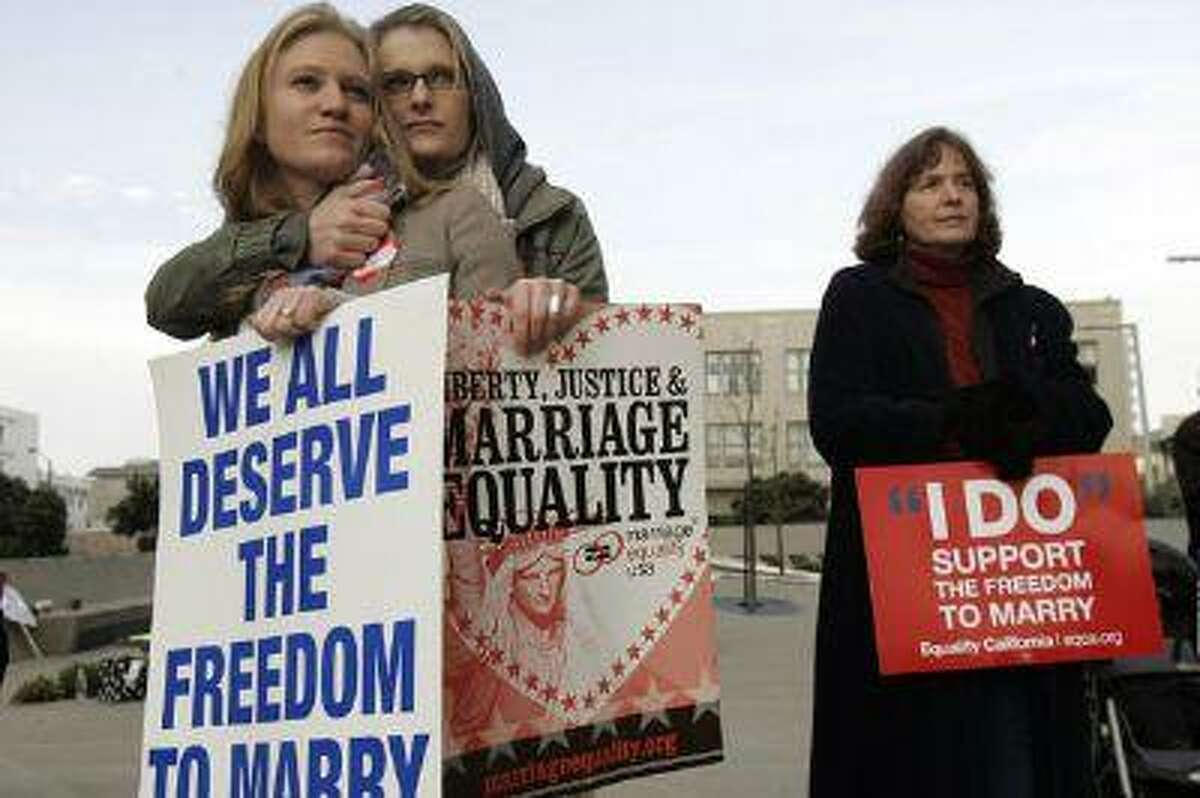 In this file photo, same-sex couple Elizabeth Chase (L) and Kate Baldridge stand outside the federal courthouse in San Francisco, Calif. (Robert Galbraith/Reuters)