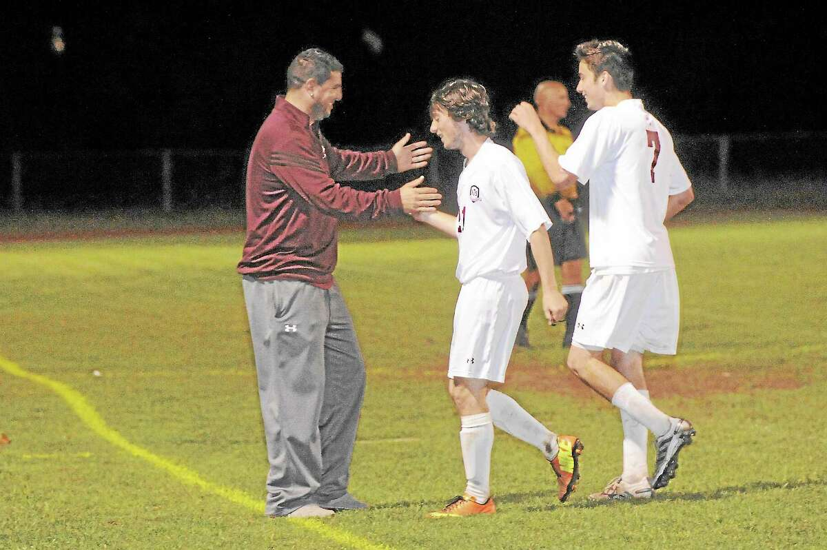 Torrington head coach Mike Fritch Jr. congratulates seniors Shane Walker (21) and Shane Bierfeldt (7) after taking them out of the last home regular season game of their careers.