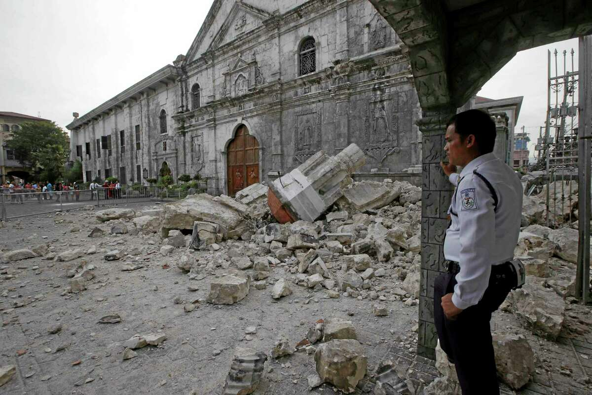 A private guard looks at the rubble near the damaged Basilica of the Holy Child, background, following a 7.2-magnitude earthquake that hit Cebu city in central Philippines and toppled the bell tower of the Philippines' oldest church Tuesday, Oct. 15, 2013. The tremor collapsed buildings, cracked roads and toppled the bell tower of the Philippines' oldest church Tuesday morning, causing multiple deaths across the central region and sending terrified residents into deadly stampedes. (AP Photo/Bullit Marquez)