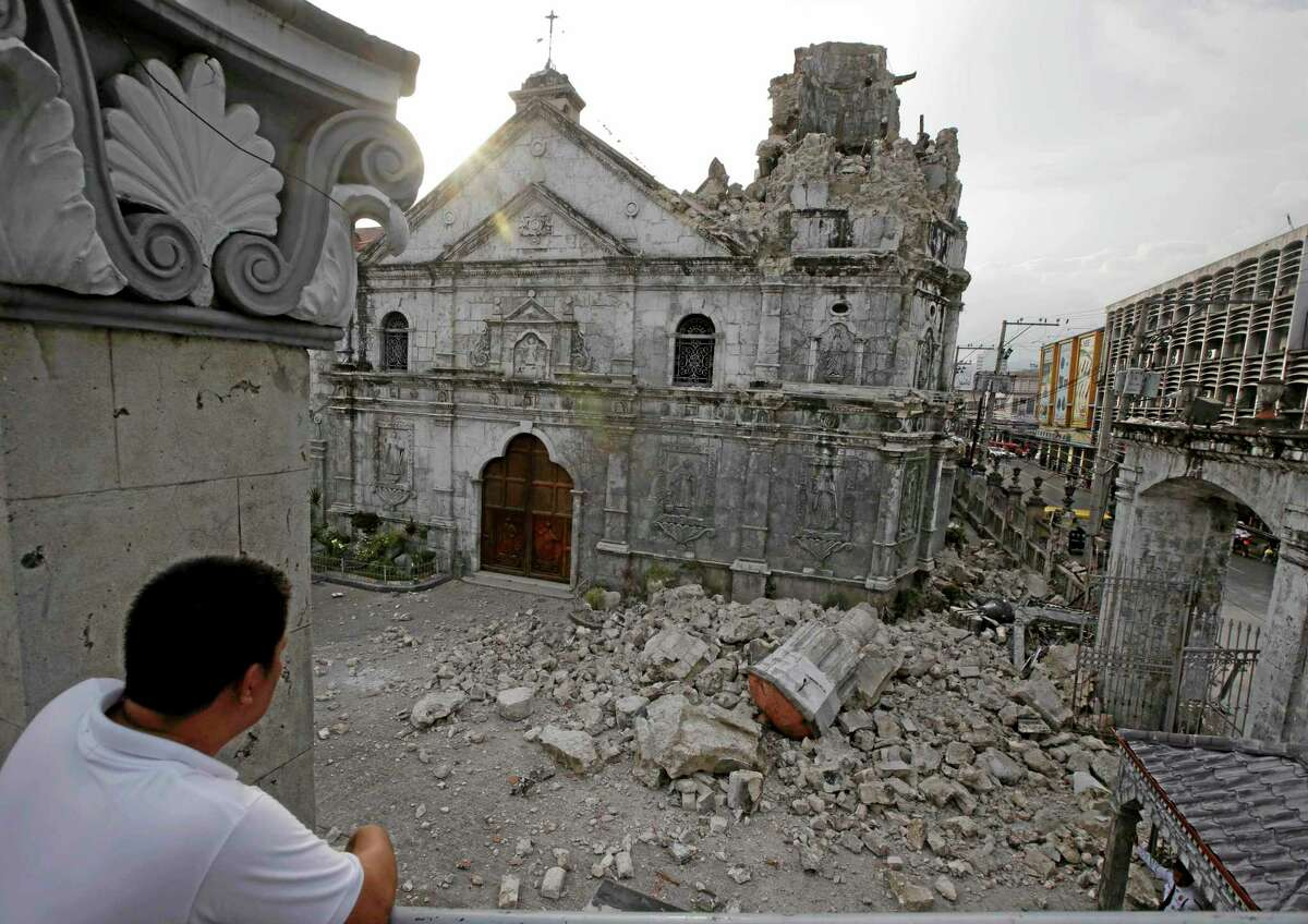 A resident looks at the rubble following a 7.2-magnitude earthquake that hit Cebu city in central Philippines and toppled the bell tower of the Philippines' oldest church Tuesday, Oct. 15, 2013. The tremor collapsed buildings, cracked roads and toppled the bell tower of the Philippines' oldest church Tuesday morning, causing multiple deaths across the central region and sending terrified residents into deadly stampedes. (AP Photo/Bullit Marquez)
