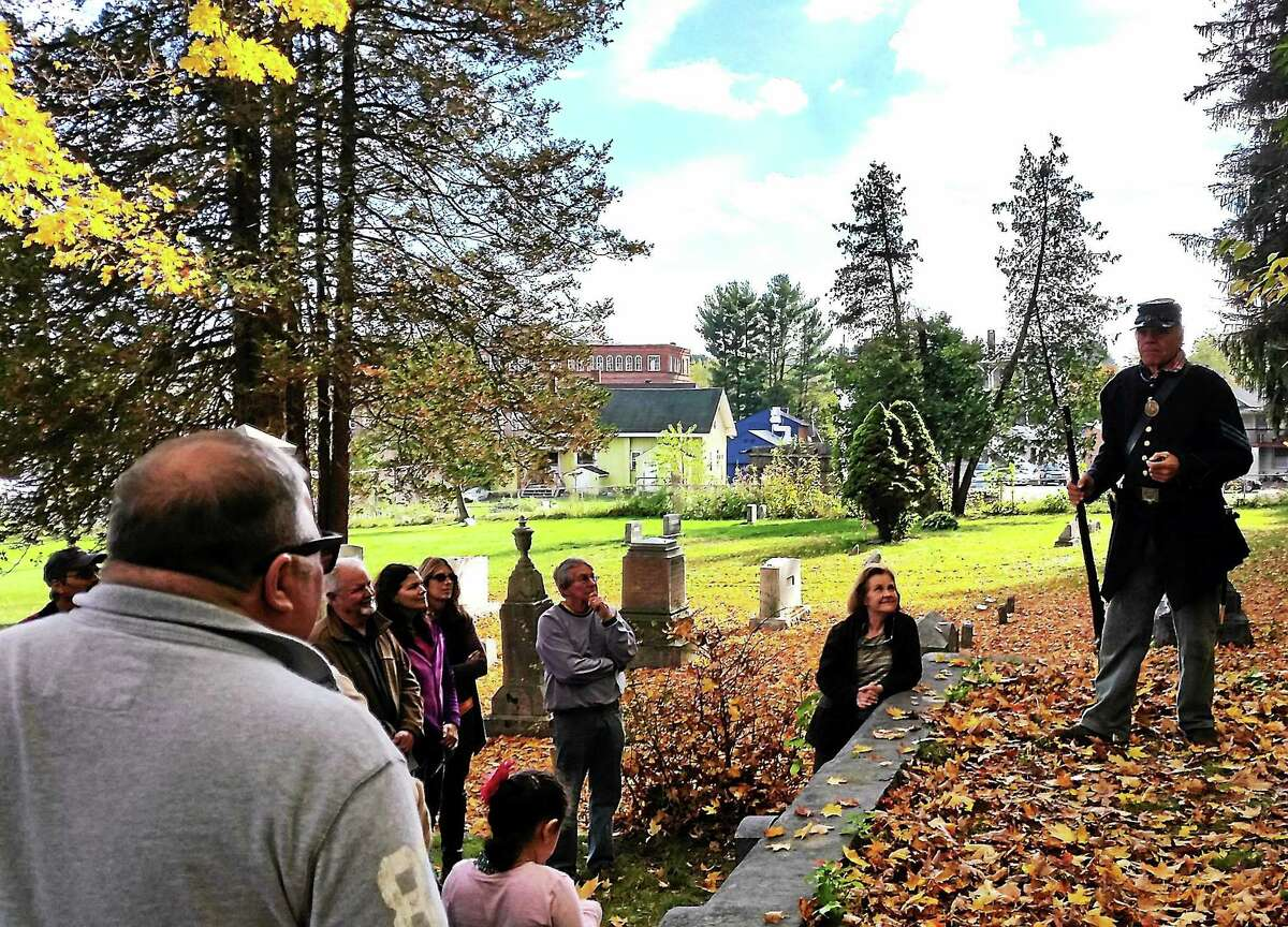 A crowd gathers to listen to one of the historical speakers during a cemetery walk in Winsted Saturday.