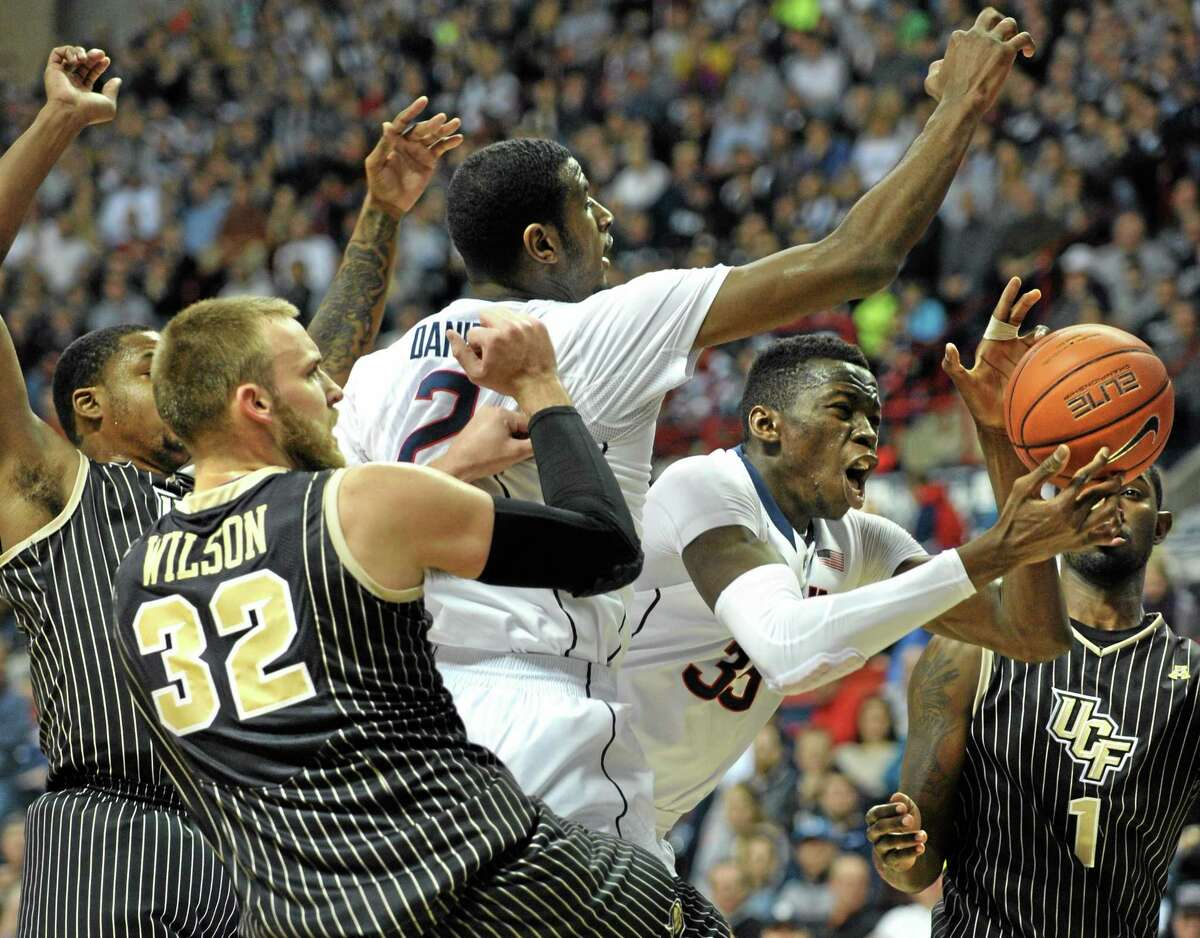 UConn's Amida Brimah (35), second from right, grabs a rebound beyond the reach of teammate DeAndre Daniels, third from right, Central Florida's Kasey Wilson (32) and Tristan Spurlock (1) during the first half of the Huskies' 84-61 win on Saturday at Gampel Pavilion in Storrs.