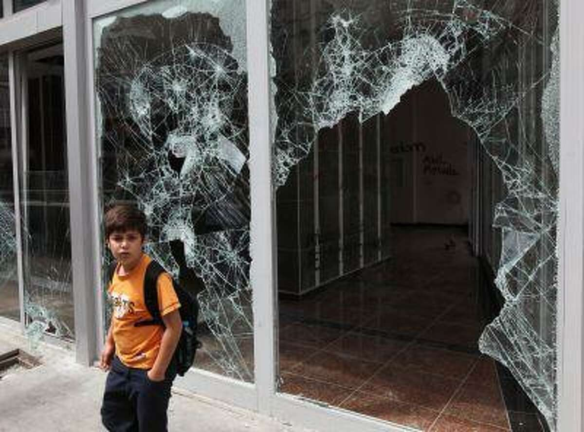 """A Turkish boy looks at destroyed shops in Ankara, Turkey, Monday, June 3, 2013. Turkish Prime Minister, Recep Tayyip Erdogan, on Monday again dismissed street protests against his rule as actions organized by extremists, qualified them as a temporary blip, and angrily rejected comparisons with the Arab Spring uprisings. Appearing defensive and angry, and cutting a disconnected figure, he lashed out at reporters who asked whether the government had understood """"the message"""" by protesters airing grievances or whether he would soften his tone.(AP Photo/Burhan Ozbilici)"""