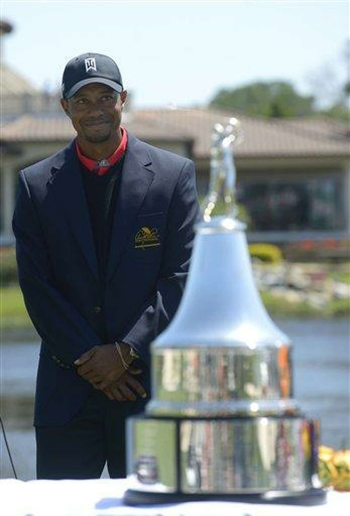 Tiger Woods stands next to the championship trophy during the awards presentation after Woods won the Arnold Palmer Invitational golf tournament in Orlando, Fla., Monday, March 25, 2013.(AP Photo/Phelan M. Ebenhack)