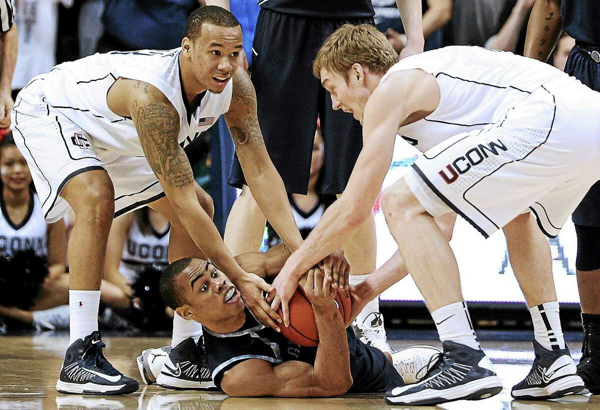 UConn's Shabazz Napier and Niels Giffey, right, reach for the ball from Georgetown's Markel Starks during the first overtime of the Hoyas' 79-78 double-OT win in Storrs on Feb. 27, 2013.