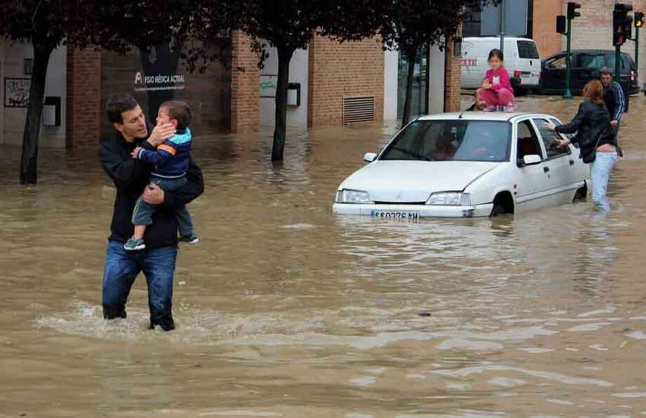 A man comforts a child rescued from a car, right, blocked on the roadside by water overflowing from the Arga River, in La Rochapea, near Pamplona northern Spain, Sunday, June 9, 2013.  Heavy rains have affected northern Spain in the last few days with flooding particularly in Navarra province. (AP Photo/Carmelo Butini) Photo: ASSOCIATED PRESS / AP2013