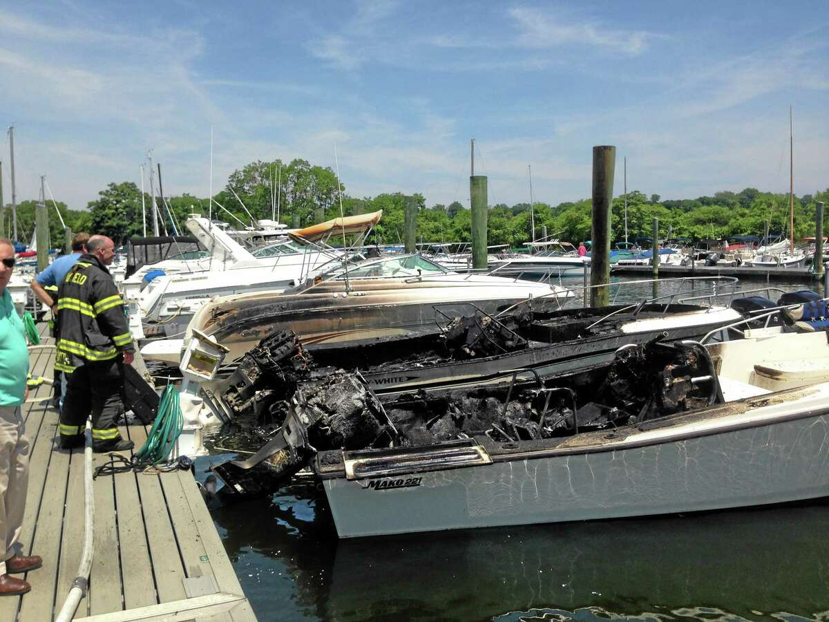 This photo provided by the Fairfield Fire Dept. shows a firefighter standing by two boats that were destroyed in a marina fire. Officials say the fire broke out Sunday, June 29, 2014 at the South Benson Marina in Fairfield, Conn.