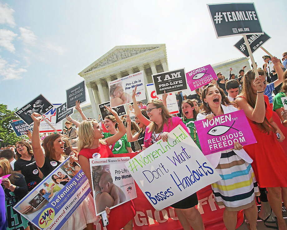 Demonstrators react to hearing the Supreme Court's decision on the Hobby Lobby case outside the Supreme Court in Washington on  June 30, 2014. The Supreme Court says corporations can hold religious objections that allow them to opt out of the new health law requirement that they cover contraceptives for women. Photo: AP Photo/Pablo Martinez Monsivais  / AP