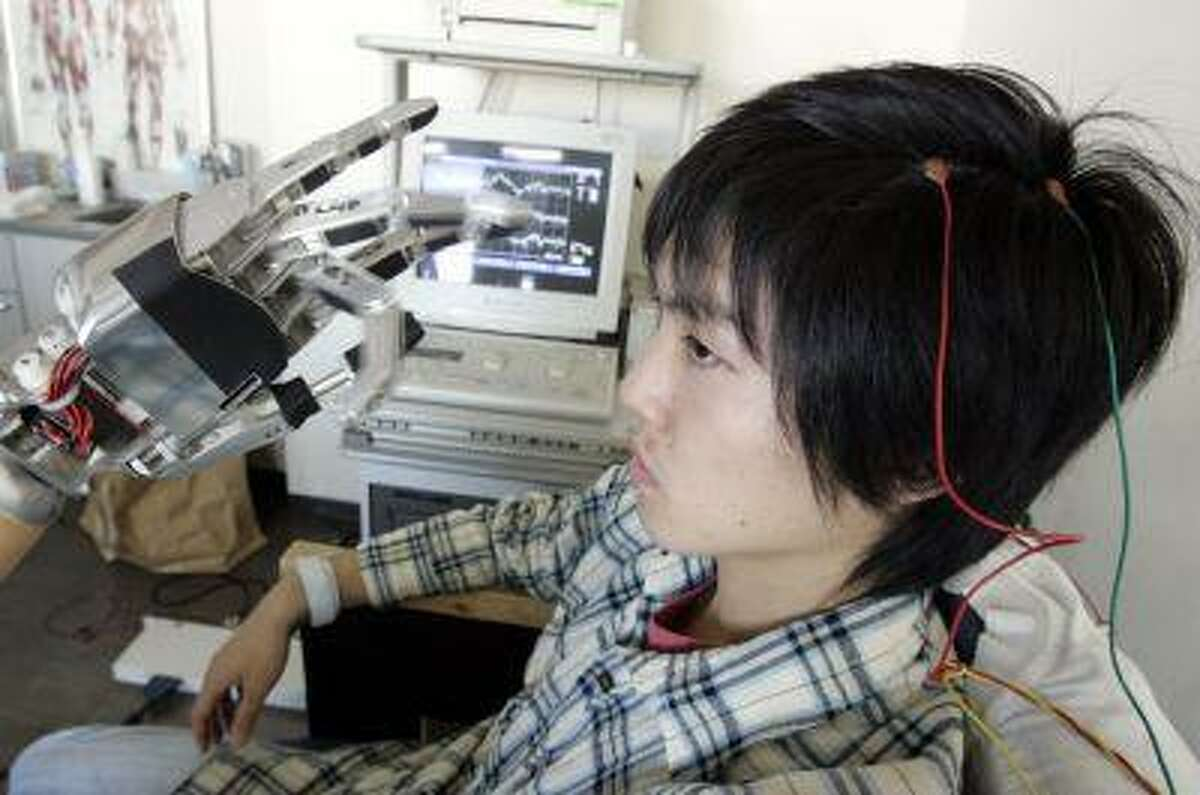 Takashi Ono moves the fingers of a robotic hand by using his brainwaves, monitored by electrodes attached to his scalp, at a Laboratory for Biomedical Engineering, Department of Biosciences and Informatics, Faculty of Science and Technology in Tokyo. (REUTERS/Yuriko Nakao)