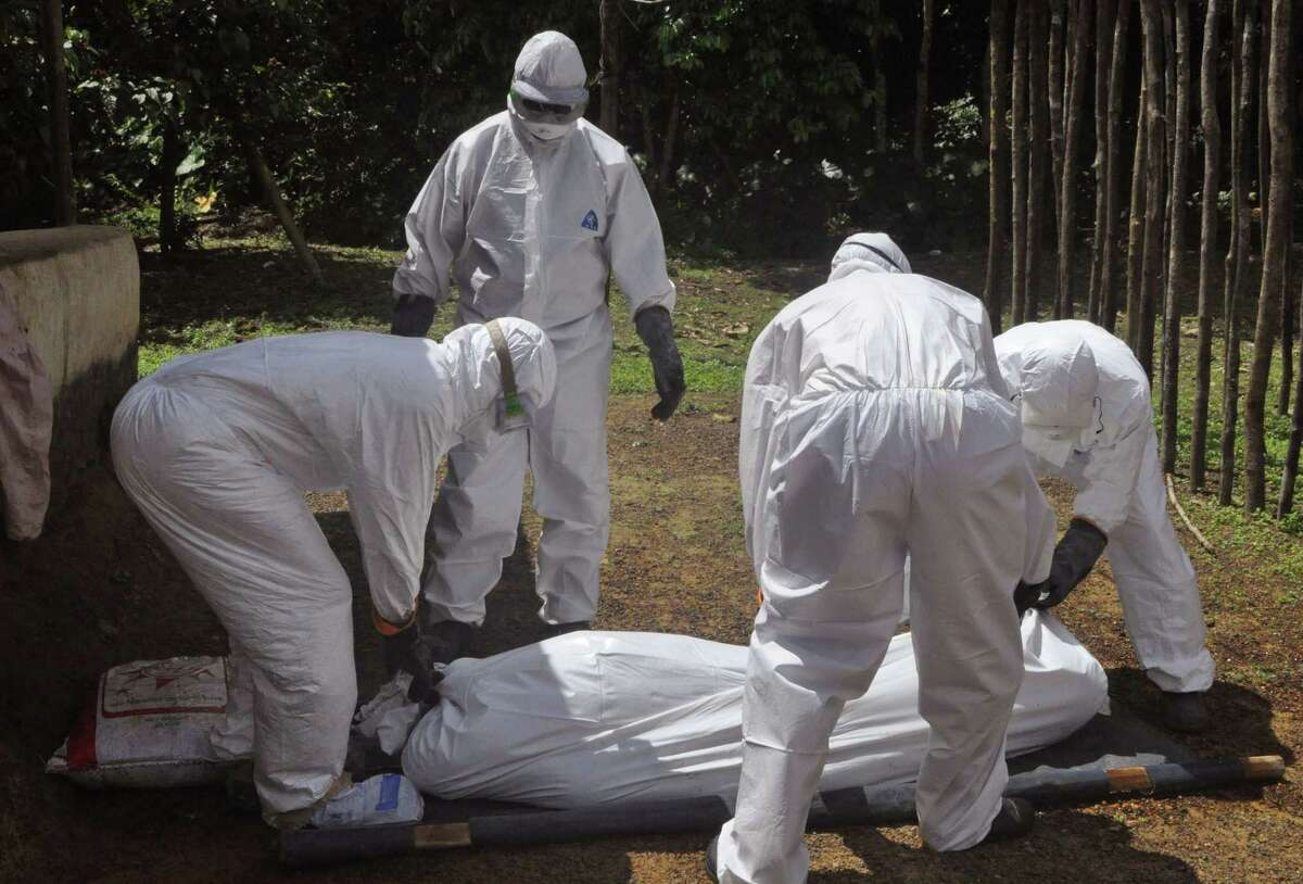 In this photo taken on Monday, Oct. 20, 2014, health workers carry the body of a woman suspected of contracting the Ebola virus in Bomi county situated on the outskirts of Monrovia, Liberia. Dozens of people quarantined for Ebola monitoring in western Liberia are threatening to break out of an isolation center in western Liberia because they have no food, the West African nationís state radio reported Thursday, Oct. 23, 2014. (AP Photo/Abbas Dulleh)