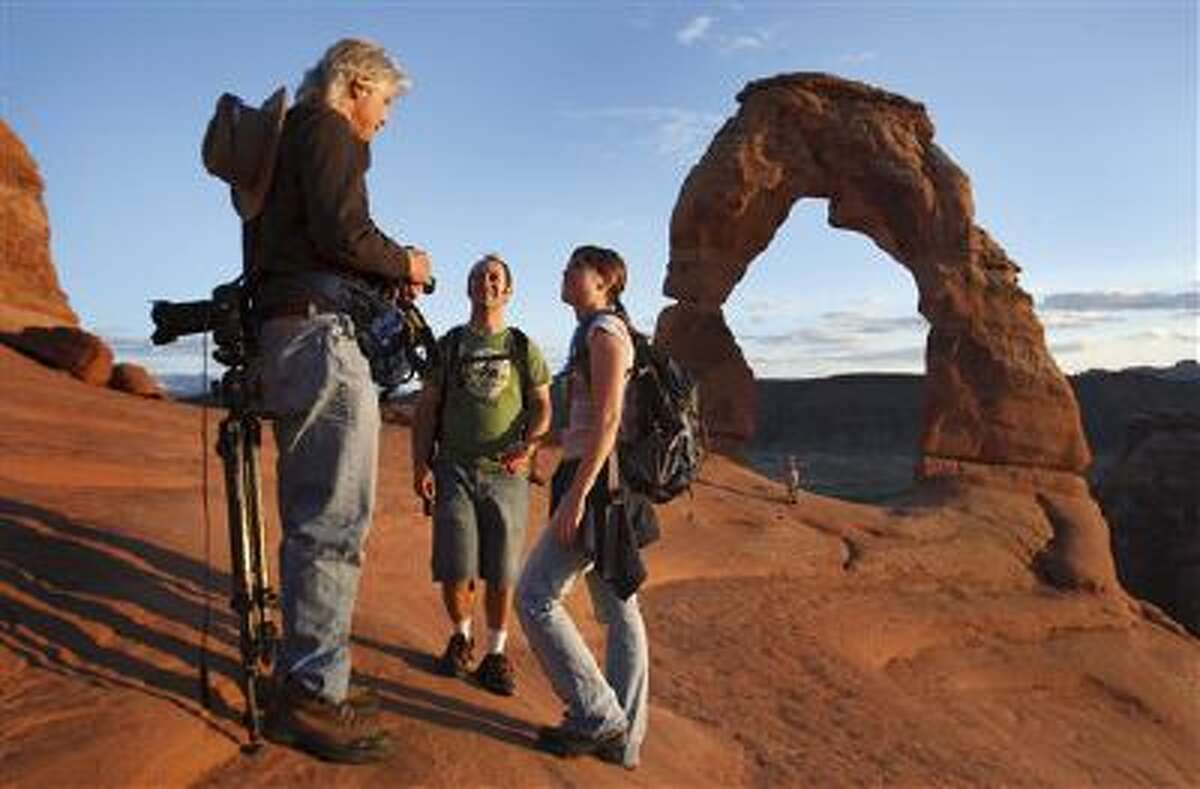 The Salt Lake Tribune Photographer Dan Caldemeyer, left, is asked to shoot a portrait at sunset. Visitors mingled around Delicate Arch to watch the sunset in the newly reopened Arches National Park last Friday. Thanks to a $1.7 million payment from Utah taxpayers, the national parks of southern Utah are being exempted from the federal government shutdown just in time for a traditionally busy fall weekend.