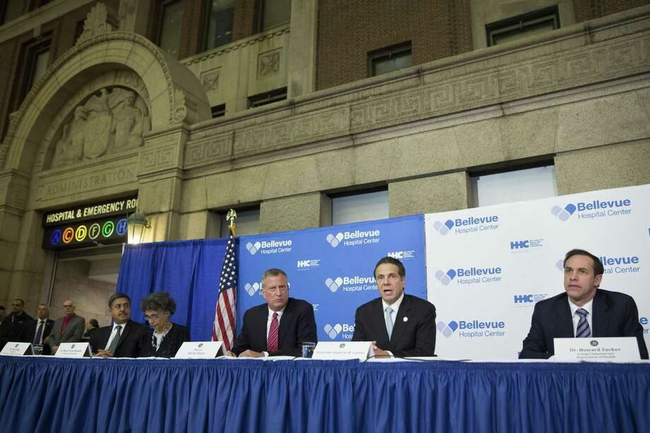 New York Gov. Andrew Coumo, center right, speaks during a news conference alongside New York City Mayor Bill de Blasio, center left, at Bellevue Hospital to discuss Craig Spencer, a Doctors Without Borders physician who tested positive for the Ebola virus, Thursday, Oct. 23, 2014, in New York. Spencer recently returned to the city after treating Ebola patients in West Africa. (AP Photo/John Minchillo) Photo: AP / FR170537 AP